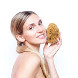 Beautiful woman with a natural sponge touching skin and smiling with teeth Stock Photography