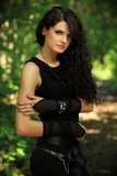 Beautiful woman in nature. Beautiful brunette in a black undershirt,    leggings and the black gloves posing in nature, forest road through the trees, greenery Stock Images