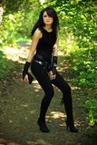 Beautiful woman in nature. Beautiful brunette in a black undershirt,    leggings and the black gloves posing in nature, forest road through the trees, greenery Stock Photo
