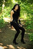 Beautiful woman in nature. Beautiful brunette in a black undershirt,    leggings and the black gloves posing in nature, forest road through the trees, greenery Royalty Free Stock Photos
