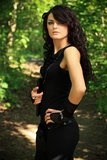 Beautiful woman in nature. Beautiful brunette in a black undershirt,    leggings and the black gloves posing in nature, forest road through the trees, greenery Stock Photos