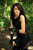 Beautiful woman in nature. Beautiful brunette in a black undershirt,    leggings and the black gloves posing in nature, forest road through the trees, greenery Royalty Free Stock Image
