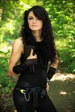 Beautiful woman in nature. Beautiful brunette in a black undershirt,    leggings and the black gloves posing in nature, forest road through the trees, greenery Royalty Free Stock Photo