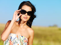 Beautiful woman on nature in black sunglasses stock photo