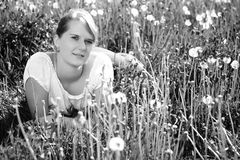 Beautiful woman in nature. Beautiful woman in white shirt lying in a grass, on a meadow, fashion photography, black and white photo, imitation of film grain Stock Images