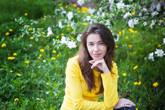 Beautiful woman near blossoming tree in spring Stock Image