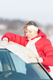 Beautiful woman near car holding map in winter. Stock Images