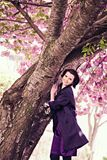Beautiful woman near cherry blossom in park Royalty Free Stock Photography