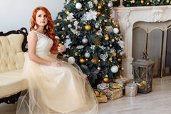 Beautiful woman near the Christmas tree in the room with fireplace royalty free stock photo