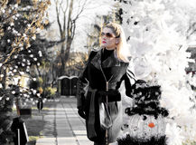 The beautiful woman near a fir-tree and a snowman, the black-and Royalty Free Stock Photo
