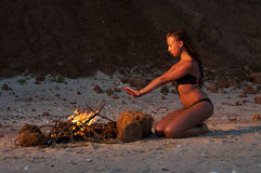 Beautiful woman near the fire on the beach. Beautiful woman in bathing suit near the fire on the beach Stock Photography