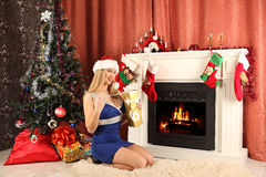 Beautiful woman near the fireplace in winter house. celebrating christmas Stock Photos