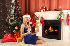 Beautiful woman near the fireplace in winter house. celebrating christmas Royalty Free Stock Photo