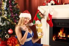 Beautiful woman near the fireplace in winter house. celebrating christmas Stock Photo
