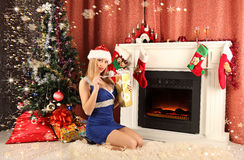 Beautiful woman near the fireplace in winter house. celebrating christmas Stock Photography