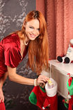 Beautiful woman near the fireplace in winter house. selebrating christmas Royalty Free Stock Photo