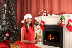 Beautiful woman near the fireplace in winter house. selebrating christmas Royalty Free Stock Photos