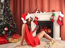 Beautiful woman near the fireplace in winter house. selebrating christmas Stock Photos