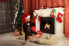 Beautiful woman near the fireplace in winter house. selebrating christmas Royalty Free Stock Image