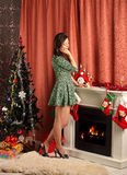 Beautiful woman near the fireplace in winter house Stock Photography