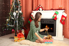 Beautiful woman near the fireplace in winter house Royalty Free Stock Images