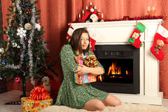 Beautiful woman near the fireplace in winter house Stock Photos