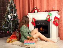 Beautiful woman near the fireplace in winter house Royalty Free Stock Photography
