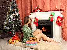 Beautiful woman near the fireplace in winter house Stock Image