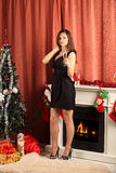 Beautiful woman near the fireplace in winter house. Studio Stock Image