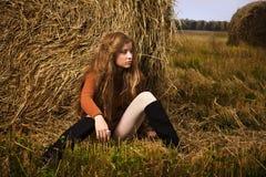 Beautiful woman near a haystack Stock Photos