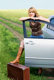 Beautiful woman near her car. Calm beautiful blond woman standing near her car with an old leathern suitcase Stock Image