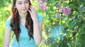 Beautiful woman near lilac tree in spring park.  stock footage