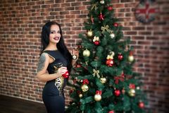 Woman near x-mas tree. Beautiful woman near x-mas tree, happy New Year party Santa girl, dreaming about presents and surprises. A large tattoo on her shoulder Royalty Free Stock Photo