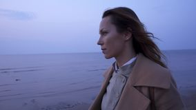 Beautiful woman near sea on a cold day stock footage