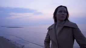 Beautiful woman near sea on a cold day stock video footage
