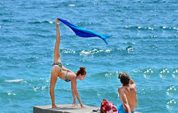 Beautiful woman near the sea. Beautiful women near the sea front of a men doing the splits Stock Images