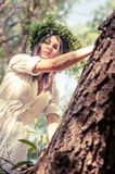 Beautiful woman near the tree in forest Stock Image