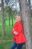 Beautiful woman near the tree in the red jacket. Photo istaken near the wood in the parc Stock Photography