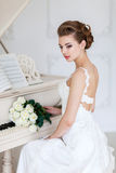 Beautiful woman near the white piano Stock Photography