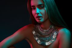 Beautiful woman in a necklace. Model in jewelry from silver. Beautiful indian jewellery. Bright lights royalty free stock photos
