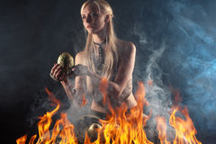 Beautiful woman with a nest egg dragons in the fire Royalty Free Stock Photos
