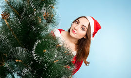Beautiful woman in new year costume with fir-tree. On blue background Royalty Free Stock Photo