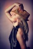 Beautiful woman in night club. Side view of beautiful woman dancing in night club, closing eyes of pleasure, wearing stylish shiny hat, celebrating new year stock image