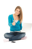 Beautiful woman with a notebook shows thumb up Royalty Free Stock Photo