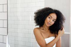 Beautiful woman observing her hair in mirror Stock Photo