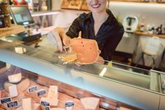 Beautiful woman offering cheese on delicatessen counter Stock Photos