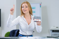 Beautiful woman at office dreaming about own home Royalty Free Stock Photography