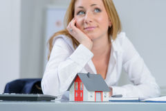 Beautiful woman at office dreaming about own home Royalty Free Stock Images