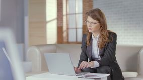 Beautiful woman office employee typing on laptop, smiling at cam. Stock footage stock video footage