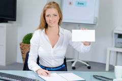 Beautiful woman at office shows  business card Royalty Free Stock Photos